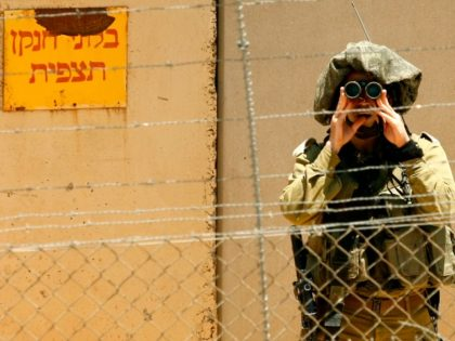 An Israeli soldier looks through his binoculars as he monitors the southern Lebanese village of Kfar Kila from the Israeli town of Metula, as seen from the Lebanese side of the border, on May 11, 2012. The Israeli military is building a wall that will run several kilometres (miles) along …