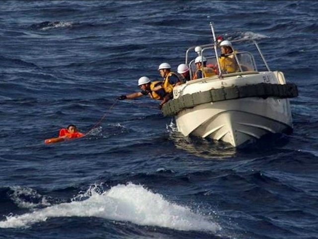 AT SEA : This handout picture taken on August 11, 2016 and released by the Japanese Coast Guard shows coast guards rescuing a crew member of a Chinese fishing boat near the waters of disputed East China Sea islands. Japan is searching for eight Chinese crew members who went missing …