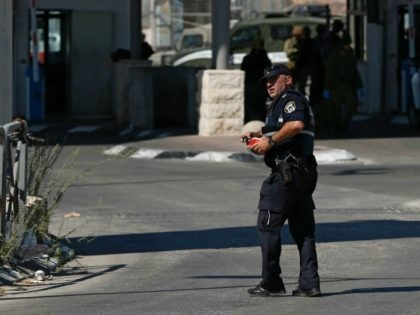 An Israeli policeman walks as security forces guard the area on July 26, 2016 at the Qalandia crossing between the West Bank city of Ramallah and Israeli-annexed east Jerusalem, after Israeli private security guards shot and wounded an 18-year-old Palestinian suspected of planning to stab them. A police statement said …