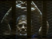 Ousted Egyptian president Mohamed Morsi gestures from the defendants cage as he attends his trial at the police academy on the outskirts of the capital Cairo on June 2, 2015. The Egyptian court postponed its final ruling on Morsi, who was sentenced to death along with dozens more over a …