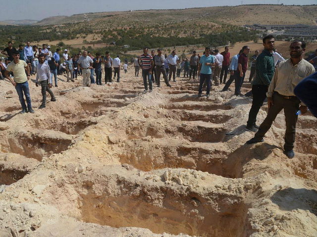 People wait close to empty graves at a cemetery during the funeral for the victims of last night's attack on a wedding party that left 50 dead in Gaziantep in southeastern Turkey near the Syrian border on August 21, 2016. At least 50 people were killed when a suspected suicide bomber linked to Islamic State jihadists attacked a wedding thronged with guests, officials said on August 21. Turkish President Recep Tayyip Erdogan said the IS extremist group was the 'likely perpetrator' of the bomb attack, the deadliest in 2016, in Gaziantep late Saturday that targeted a celebration attended by many Kurds. / AFP / ILYAS AKENGIN (Photo credit should read ILYAS AKENGIN/AFP/Getty Images)