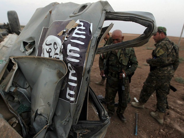 IRAQ, Mosul : Peshmerga fighters inspect the remains of a car, bearing an image of the trademark jihadist flag, which belonged to Islamic State (IS) militants after it was targeted by an American air strike in the village of Baqufa, north of Mosul, on August 18,2014. Kurdish peshmerga fighters backed …