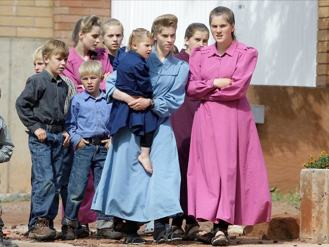 FILE - In this Sept. 15, 2015, file photo, onlookers watch as crews clear mud and debris from a road following a flash flood, in Colorado City, Ariz. The number of babies born in the polygamous town on the Utah-Arizona border declined from 2009 to 2013 — a time period …