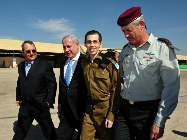 In this handout photo provided by the Israeli Defence Force, freed Israeli soldier Gilad Shalit (2nd R) walks with Defence Minister Ehud Barak (L), Israeli Prime Minister Benjamin Netanyahu (2nd, L) and IDF Chief of General Staff Benny Gantz (R) at Tel Nof Airbase on October 18, 2011 in central …