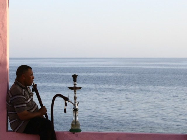 Two men sit on wall overlooking the Red Sea at a popular cafe in the northwestern Saudi town of al-Wajh on April 25, 2016.