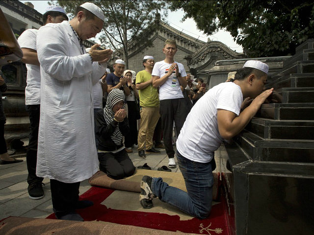 Muslim pray before the Shaykhs tombs, relics from the 13th century, after Eid al-Fitr prayers at the Niujie mosque, the oldest and largest mosque in Beijing, China, Wednesday, July 6, 2016. The Eid al-Fitr celebrations mark the end of the Muslim holy fasting month of Ramadan. (AP Photo/Ng Han Guan)