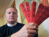 In this July 27, 2016 photo, Rev. Jeremy Lucas of Christ Church Episcopal Parish holds the 150 tickets that he purchased in an all-star softball team's raffle to win an AR-15 assault rifle in Lake Oswego, Ore. Lucas may have run afoul of Oregon law when he transferred the assault rifle, which he says he tried to win in order to destroy it, to a friend for safekeeping without performing a background check. (Vern Uyetake/Lake Oswego Review via AP)