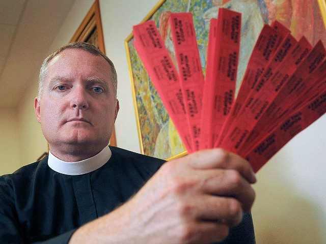In this July 27, 2016 photo, Rev. Jeremy Lucas of Christ Church Episcopal Parish holds the 150 tickets that he purchased in an all-star softball team's raffle to win an AR-15 assault rifle in Lake Oswego, Ore. Lucas may have run afoul of Oregon law when he transferred the assault …