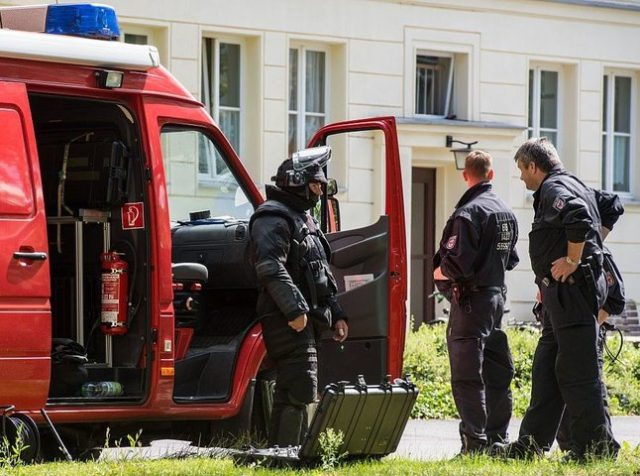 Officers of a special task force stand in front of an apartment building in Eisenhuettenstadt, eastern Germany, on August 17, 2016. German police has arrested a 27-year old man who is suspected of having planned an explosives attack on a street festival, local authorities said. / AFP / dpa / …