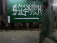 A man walks beside the Saudi flag at the popular market of Qabil street in the heart of Jeddah historic center on December 9, 2015 in Jeddah, Saudi Arabia. The street which is one of the oldest business streets that dates back to early days of 20th century, got its …