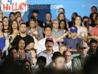 A man identified as Seddique Mateen (C-red ball cap), whose son shot and killed 49 people and injured 53 others inside the Pulse nightclub in June, sits with supporters at a rally for Democratic Presidential nominee Hillary Clinton at the Osceola Heritage Park in Kissimmee, Florida on August 8, 2016. …