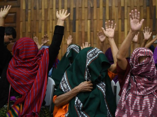 Victims of sexual abuse, who cover their faces to hide their identities, celebrate after a judge declared two former military men guilty of keeping 11 indigenous women as sex slaves during Guatemala's civil war, in a courtroom in Guatemala City, February 26, 2016.