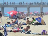 Beachgoers and sunbathers crowd Huntington Beach, California on July 22, 2016 during a southern California heatwave where temperatures topped 100 degrees in some areas as the National Weather Service issued an excessive heat warning for the valleys and mountains into the weekend. The weeklong 2016 Vans US Open of Surfing …