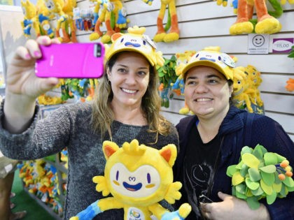 Shoppers at a megastore in Rio de Janeiro that sells official products for the 2016 Olympic and Paralympic Games wear hats in the shape of Vinicius, the official mascot of the Rio Olympics, as they pose for a photo on July 17, 2016 ahead of the opening of the Summer …