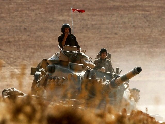 Turkish soldiers hold their position on a tank as they watch the town of Kobani from near the Mursitpinar border crossing, on the Turkish-Syrian border in the southeastern town of Suruc in Sanliurfa province October 13, 2014. The strategic border town of Kobani has been beseiged by Islamic State militants …