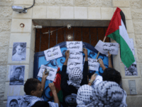 Masked Palestinian youths place slogans near pictures of Palestinians who died during violence between Palestinians and Israel, as they gather in front of the UNDP (United Nations Development Programme) offices in Gaza City to support Palestinians living in the Israeli-occupied West Bank, on Novembre 2, 2015.