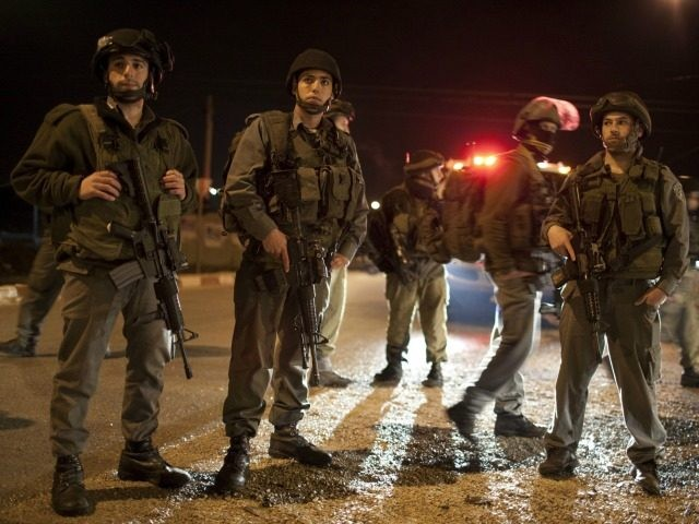 Israeli soldiers block the road in the Hawara checkpoint south of the West Bank city of Nablus on March 12,2011 after a Palestinian killed five Israelis in an overnight attack in the Jewish settlement of Itamar, in the Israeli-occupied occupied West Bank. According to media reports the vicitms were all …