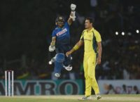 Sri Lanka batsman Dinesh Chandimal (L) celebrates his century as Australian cricketer Mitchell Starc looks on during the third ODI in Dambulla on August 28, 2016