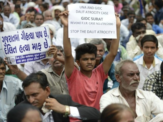 """An Indian member of the Dalit caste community holds a placard reading, """"In Gujarat, Cow Slaughter is a Sin while Killing Dalits is pardonable"""" (L) as he participates in a protest rally against an attack on Dalit caste members on July 31, 2016"""