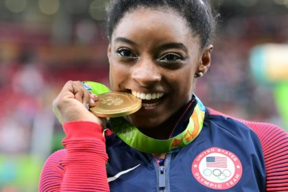 US gymnast Simone Biles celebrates with her gold medal after the women's individual all-around final in Rio on August 11, 2016