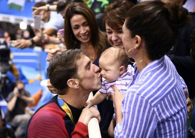 USA's Michael Phelps (L) kisses his son Boomer next to his partner Nicole Johnson (R) and mother Deborah (C) after he won the men's 200m butterfly final on August 9, 2016