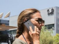 An Israeli woman uses her iPhone in front of the building housing the Israeli NSO group, on August 28, 2016, in Herzliya, near Tel Aviv
