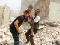 Syrians carry a wounded child in the rubble of buildings following a barrel bomb attack on the Bab al-Nairab neighbourhood of the northern Syrian city of Aleppo on August 25, 2016