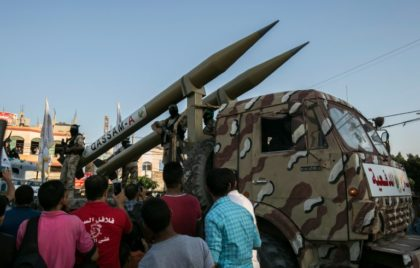 Palestinian members of the al-Qassam Brigades, the armed wing of the Hamas movement, display home-made rockets during an anti-Israel parade in Rafah in the southern Gaza Strip