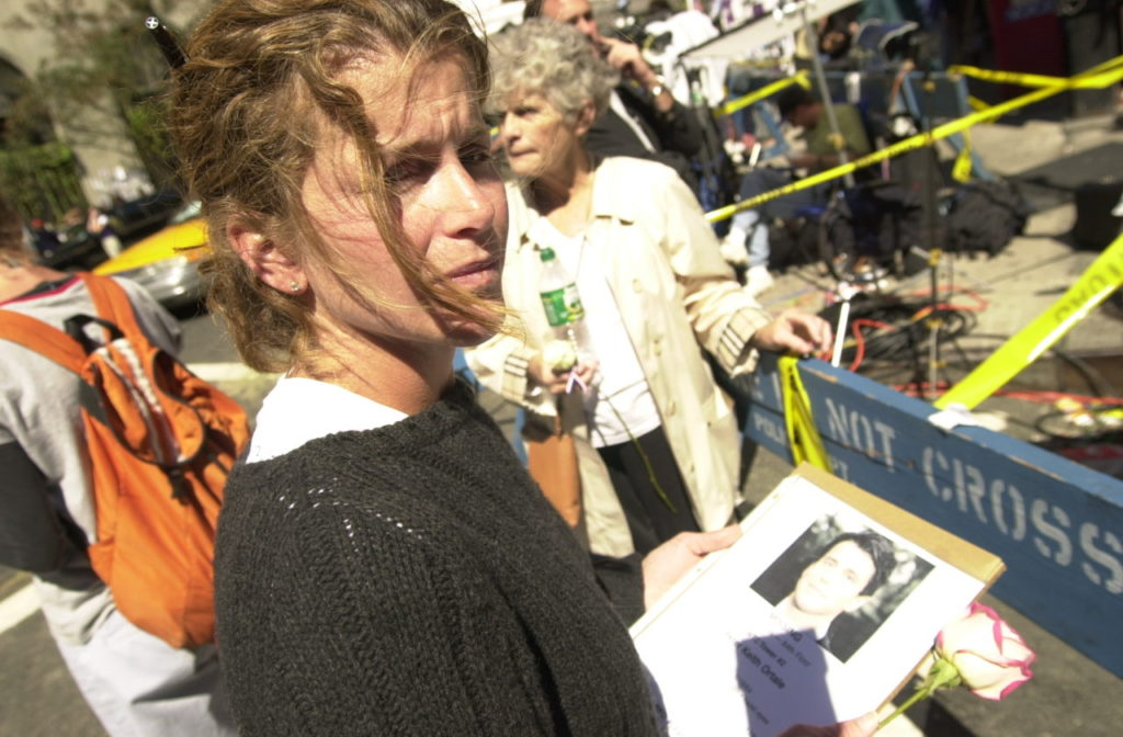 In this September 15, 2001 photograph, a woman poses with a picture of a missing loved one who was last seen at the World Trade Center when it was attacked on September 11, 2001.(AP Photo/Charlie Krupa)