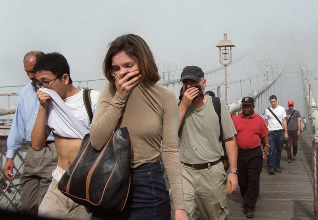 People cover their faces as they move across the Brooklyn Bridge out of the smoke and dust in Manhattan Tuesday Sept. 11, 2001, after a terrorist attack on the twin towers of the World Trade Center. Terrorists hijacked two airliners and crashed them into the World Trade Center in a coordinated series of blows that brought down the twin 110-story towers. (AP Photo/Daniel Shanken)