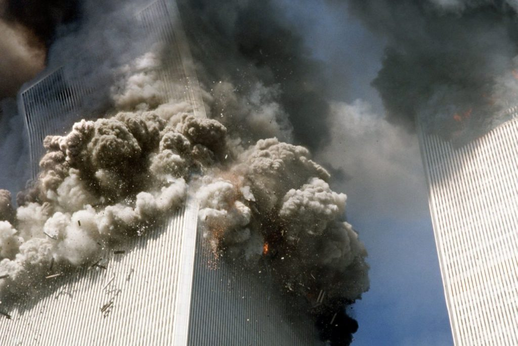 The south tower of the World Trade Center, left, begins to collapse after a terrorist attack on the landmark buildings in New York, Tuesday, Sept. 11, 2001. (AP Photo/Gulnara Samoilova)