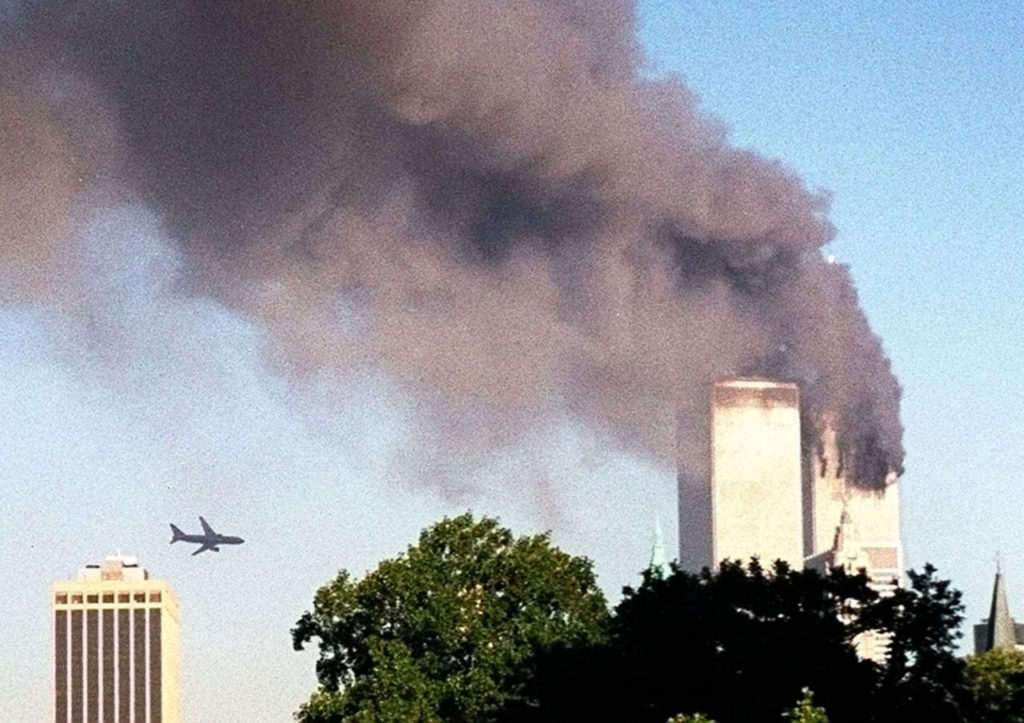 A plane approaches New York's World Trade Center moments before it struck the tower at left, as seen from downtown Brooklyn, Tuesday, Sept. 11, 2001. In an unprecedented show of terrorist horror, the 110 story towers collapsed in a shower of rubble and dust after 2 hijacked airliners carrying scores of passengers slammed into them. (AP Photo/ William Kratzke)