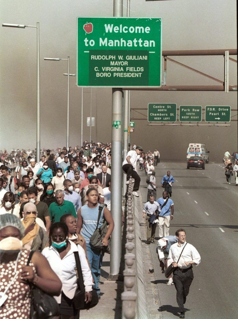 People flee lower Manhattan across the Brooklyn Bridge in New York, Tuesday, Sept. 11, 2001, following a terrorist attack on the World Trade Center. (AP Photo/Daniel Shanken) MANDATORY CREDIT