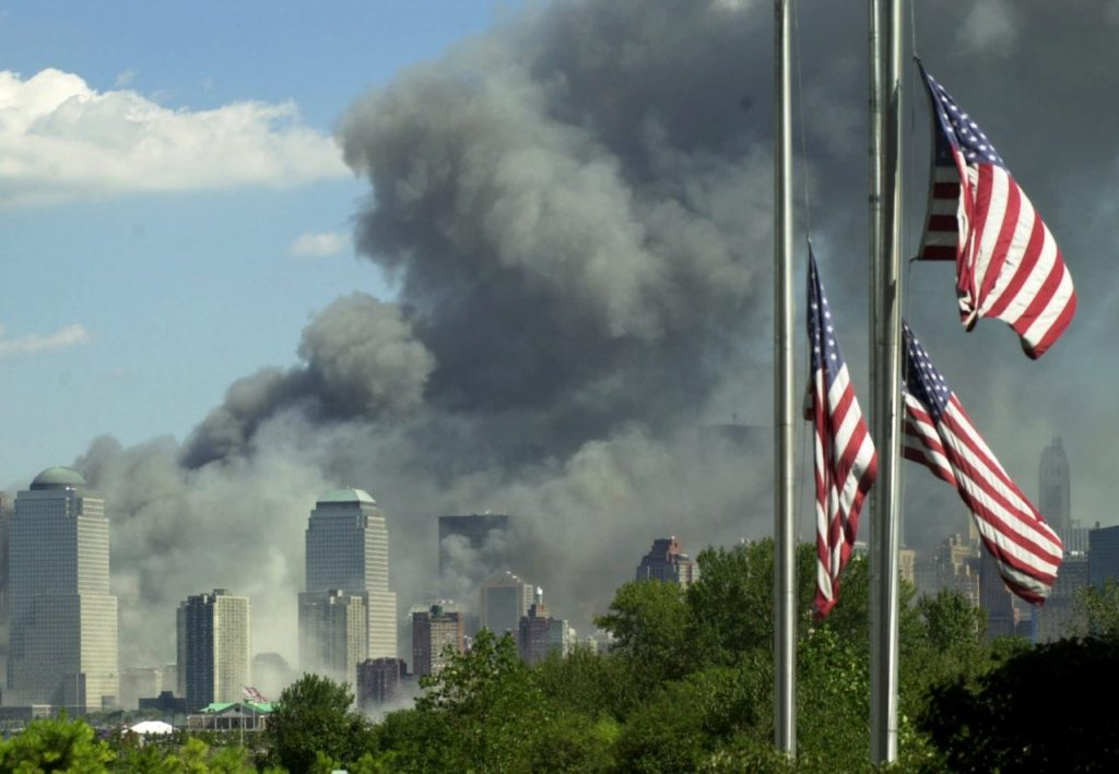 Flags fly at half-staff at the Liberty Science Center in Jersey City, N.J. as a large cloud of smoke billows from a fire at the World Trade Center in New York, Tuesday, Sept. 11, 2001. In one of the most devastating attacks ever against the United States, terrorists crashed two airliners into the World Trade Center in a closely timed series of blows that brought down the twin 110-story towers. (AP Photo/Daniel Hulshizer)