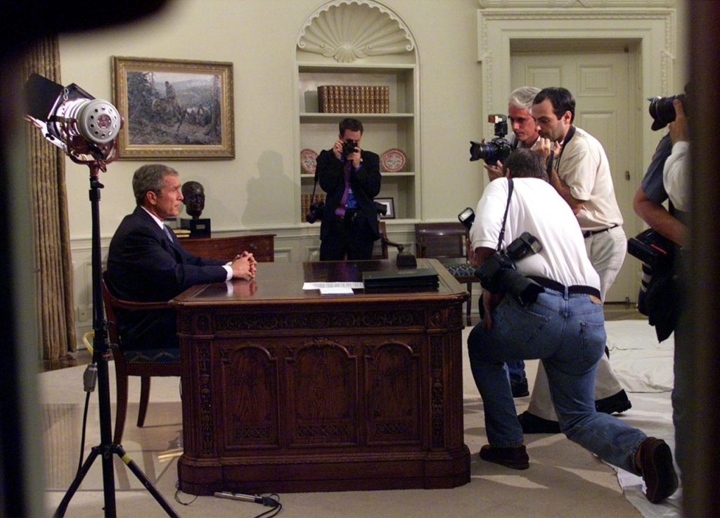 President Bush is seen through the windows of the Oval Office of the White House in Washington, Tuesday, Sept. 11, 2001, as he addresses the nation about terrorist attacks at the World Trade Center and the Pentagon. (AP Photo/Doug Mills)
