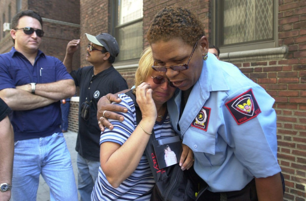 In this September 13, 2001 photograph, a woman is comforted as she holds a picture of a missing loved one who was last seen at the World Trade Center when it was attacked on September 11, 2001.(AP Photo/Kathy Willens)