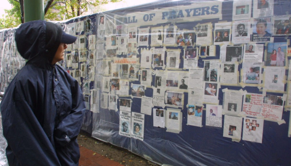 A woman looks at missing person posters of victims of the September 11 terrorist attacks on the World Trade Center in New York City on Sept. 14, 2001.(AP Photo/Robert Spencer)