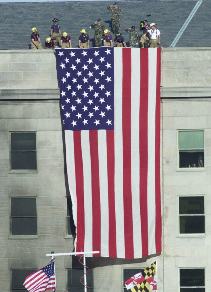 Firefighters unfurl an American flag from the roof of the Pentagon Wednesday, Sept. 12, 2001, as President Bush visits the area of the Pentagon where an airliner, hijacked by terrorists, crashed into the building on Tuesday. (AP Photo/Ron Edmonds)