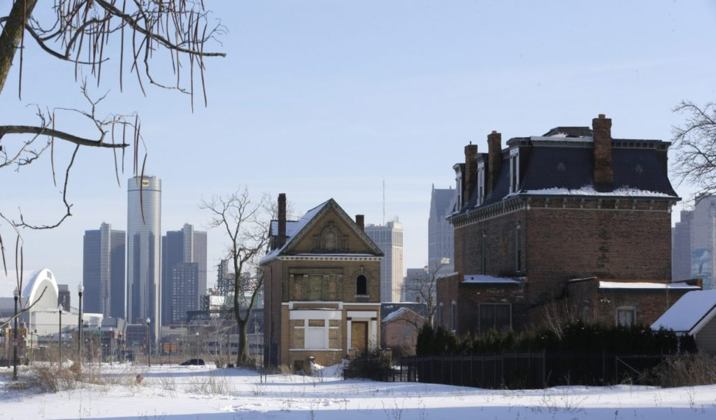 FILE - This Feb. 13, 2014 photo shows a boarded up house in Detroit's Brush Park neighborhood, with the General Motors headquarters at background left. From 2000 to 2010 alone, the city lost about a quarter-million residents. (AP Photo/Carlos Osorio)