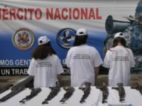 Four alleged members of the Revolutionary Armed Forces of Colombia (FARC) stand by weapons as they are presented to the press at a military base in Medellin, Colombia, Saturday Aug. 28, 2010.