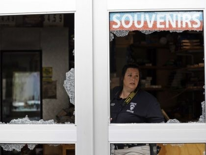 A crime scene photographer looks out a storefront damaged overnight by protesters following Tuesday's police shooting of Keith Lamont Scott in Charlotte, N.C., Thursday, Sept. 22, 2016. Charlotte's police chief said Thursday he plans to show video of an officer shooting Scott to his family, but the video won't be …