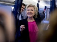 Democratic presidential candidate Hillary Clinton, accompanied by Traveling Press Secretary Nick Merrill, left, smiles as she speaks to members of the media as her campaign plane prepares to take off at Westchester County Airport in Westchester, N.Y., Tuesday, Sept. 6, 2016, to head to Tampa for a rally in Tampa. …