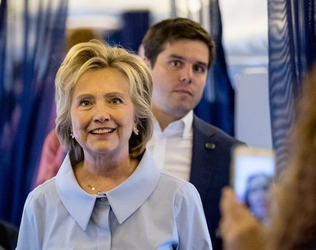 Democratic presidential candidate Hillary Clinton accompanied by traveling press secretary Nick Merrill, right, comes back to speak to members of the media on board for her first flight on a new campaign plane before taking off at the Westchester County Airport in White Plains, N.Y., Monday, Sept. 5, 2016, to …