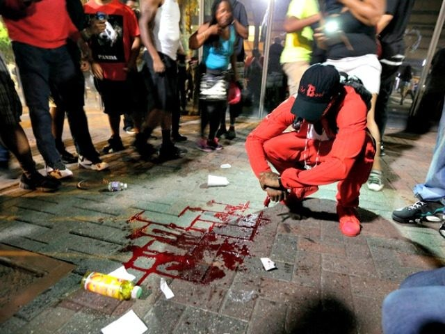 A man squats near a pool of blood after a man was injured during a protest of Tuesday's fatal police shooting of Keith Lamont Scott in Charlotte, N.C. on Wednesday, Sept. 21, 2016. Protesters rushed police in riot gear at a downtown Charlotte hotel and officers have fired tear gas …