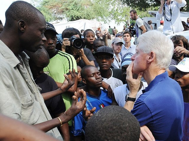 Former US president and UN Special Envoy for Haiti Bill Clinton (R) listens to local residents on October 6, 2010 in a city camp in Port-au-Prince. The Clinton Foundation announced that it will, through its Haiti Relief Fund - provide 500,000 USD in bridge funding for a camp in Petionville …