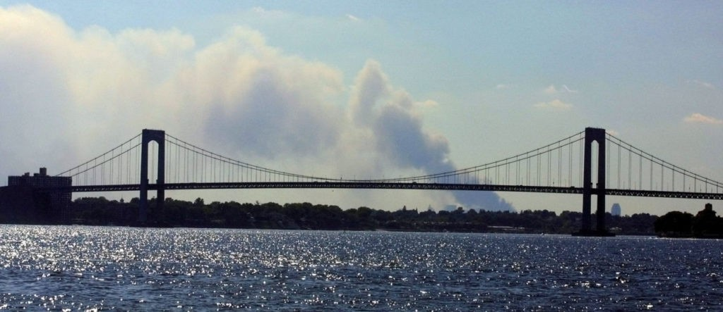 Smoke rises in the distance before the Long Island and the Throgs Neck Bridge 11 September 2001 between the Bronx and Queens, NY, following the destruction of the the twin towers of the World Trade Center. An apparent terrorist attack leveled the two buildings. AFP PHOTO/Matt CAMPBELL (Photo credit should read MATT CAMPBELL/AFP/Getty Images)