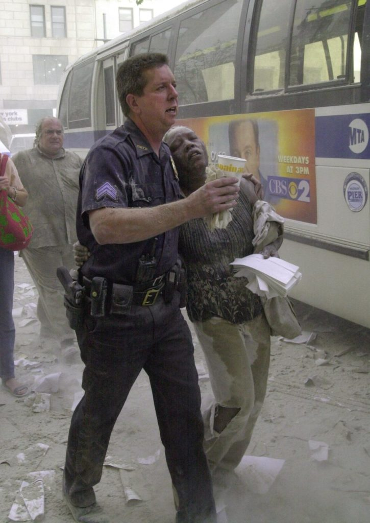 A police officer helps a woman to a bus after she fled the area near the World Trade Center towers 11 September, 2001, in New York. Two planes crashed into each building and the tops of each tower later collapsed AFP PHOTO/Stan HONDA (Photo credit should read STAN HONDA/AFP/Getty Images)
