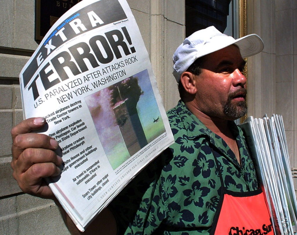 "Newspaper vendor Carlos Mercado sells the ""Extra"" editon of the Chicago Sun-Times printed 11 September, 2001, after the terrorist attacks on the United States. Two hijacked airplanes crashed into the World Trade Center twin towers in New York while one hijacked plane later crashed at the Pentagon in Washington, DC, with another plane crashing 80 miles outside of Pittsburgh, Pennsylvania. AFP PHOTO/Scott OLSON (Photo credit should read SCOTT OLSON/AFP/Getty Images)"