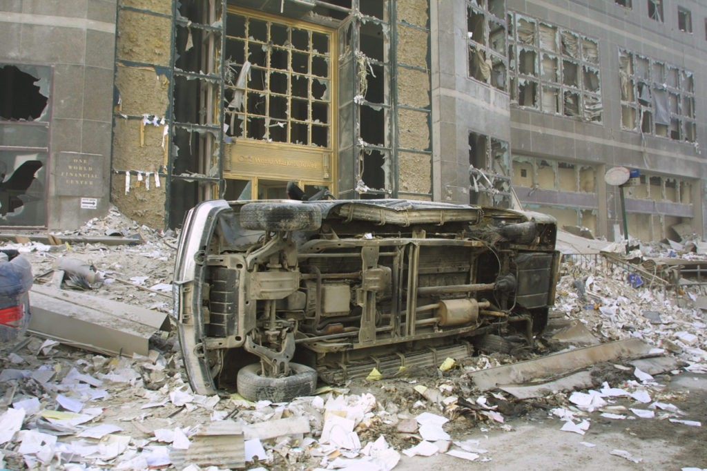 394277 05: A car sits on its side amid rubble at the World Trade Center after two hijacked planes crashed into the Twin Towers September 11, 2001 in New York. (Photo by Ron Agam/Getty Images)