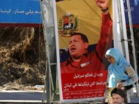 "A Lebanese Shiite woman, holding a picture of Hassan Nasrallah, the Secretary General of Hezbollah, walks in front of a poster showing Venezuela's President Hugo Chavez and a slogan that reads: ""Gracias Chavez"" 21 September 2006 at the southern suburb of Beirut. Chavez stunned the UN General Assembly with a …"